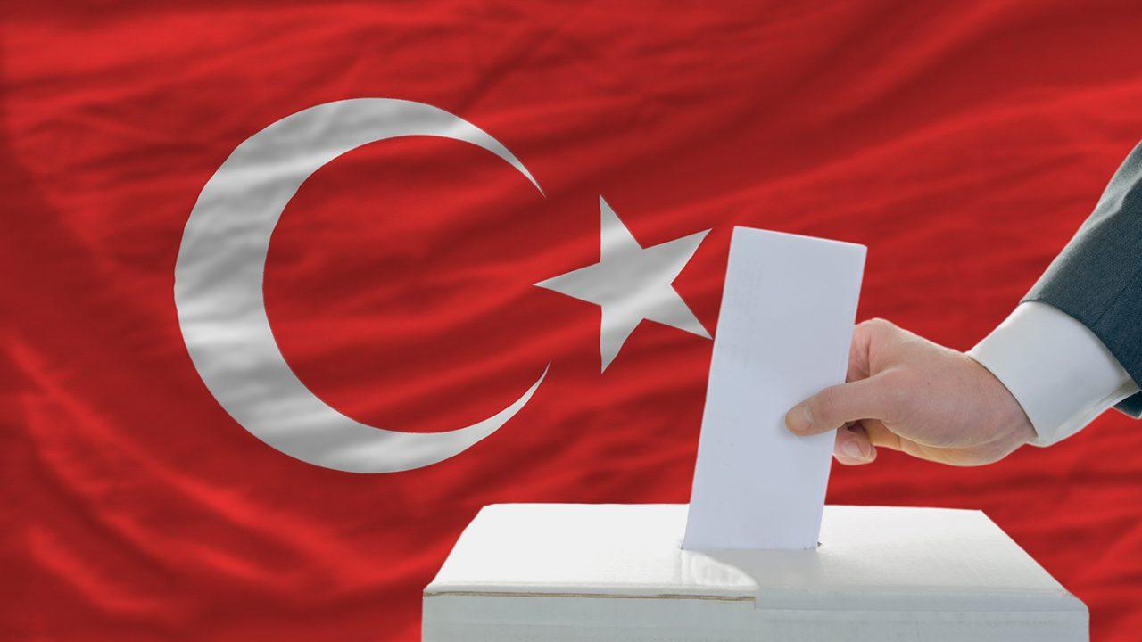 Stimmzettel wird in Wahlurne geworfen, die vor der türkischen Flagge steht