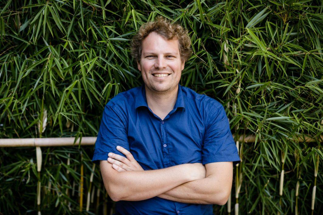 Felix Creutzig verschränkt die Arme und lächelt. Pflanzen sind im Hintergrund.