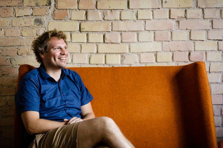 Prof. Dr. Felix Creutzig sitzt auf einem orangen Sofa und lächelt