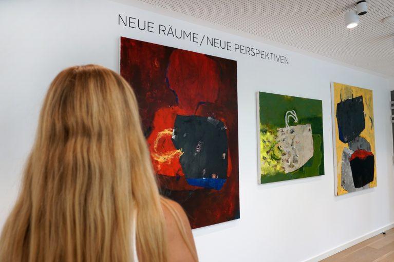Eine Frau betrachtet Gemälde von Maritta Iseler