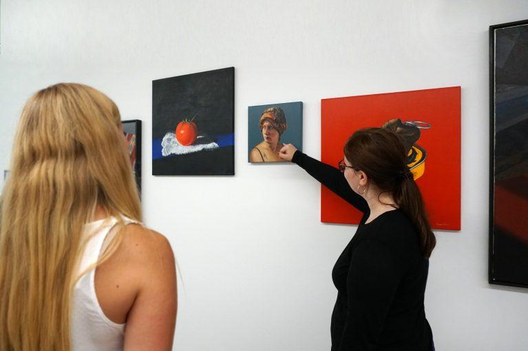 Zwei Frauen betrachten Gemälde von Maritta Iseler