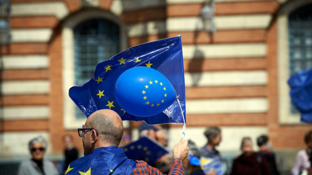 Mann mit zwei EU-Flaggen und einem EU-Ballon