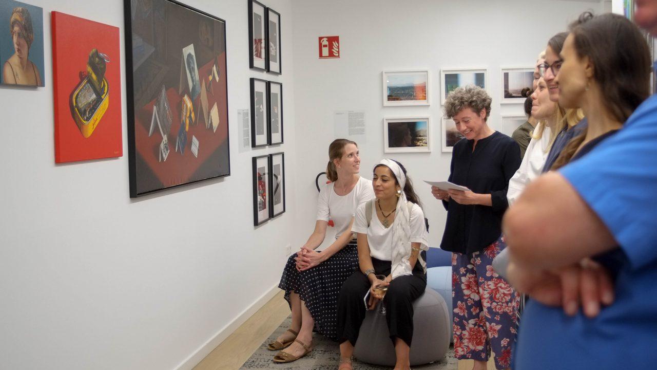 Eine Menschengruppe betrachtet Bilder in einer Galerie