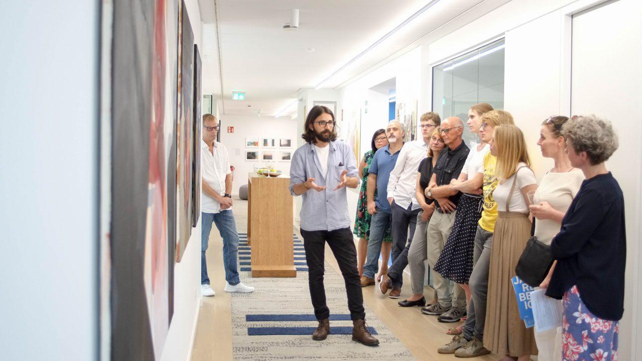 """Eine Gruppe von Menschen hat sich zu einer Diskussion vor ein paar Bildern der Ausstellung """"Neue Räume/Neue Perspektiven"""" versammelt."""