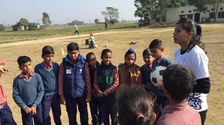 Eine Fußballtrainerin mit verschiedenen Kindern