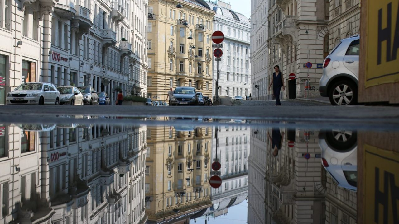 Spiegelung von Gebäuden einer Straße in Budapest in einer großen Pfütze.