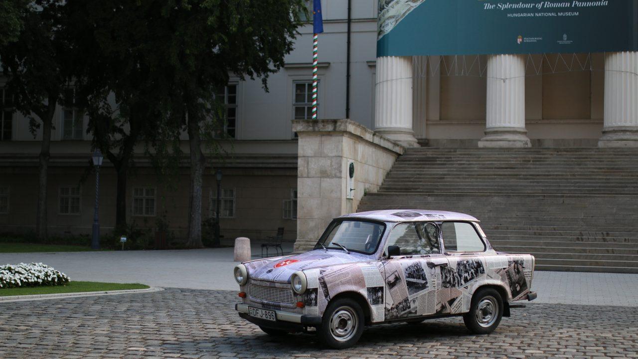 Ein Auto mit einem Zeitungspapieraufdruck steht vor dem ungarischen National Museum in Budapest.