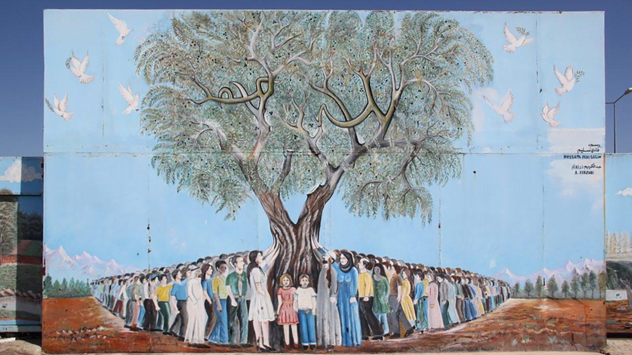 Eine Wandmalerei: Menschen versammeln sich um einen Baum.