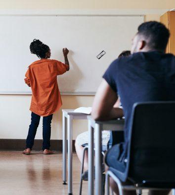 Eine Lehrerin schreibt etwas an die Tafel.