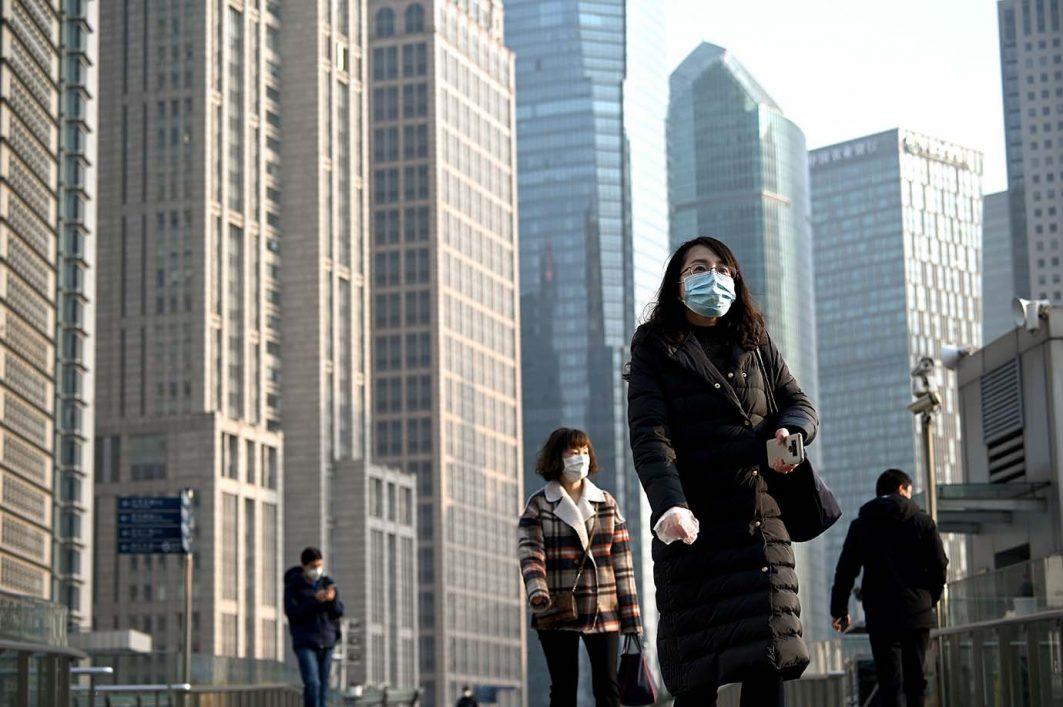 Leute tragen Schutzmasken in einer Fußgängerzone in Shanghai