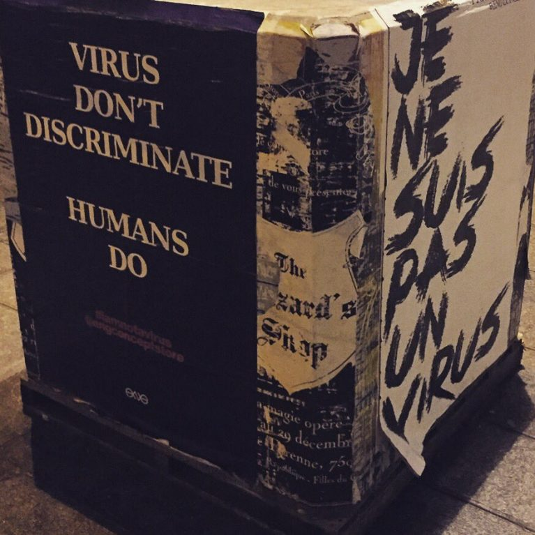 "Buch mit der Aufschrift ""Virus don't discriminate. Humans do"""