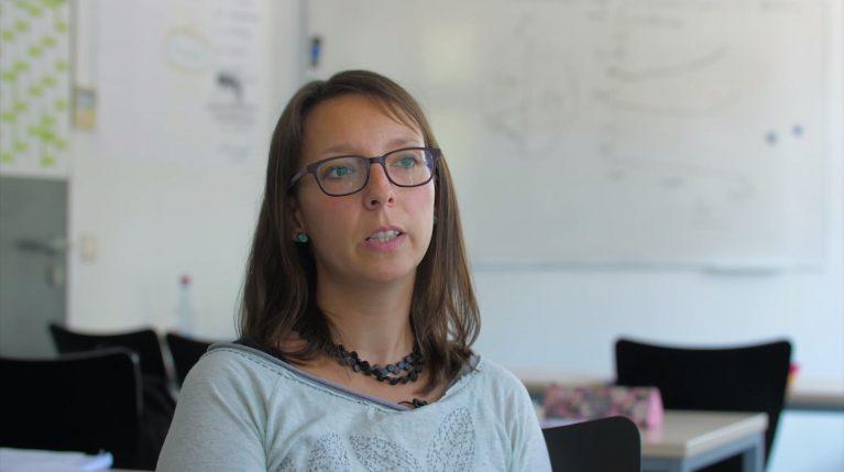 Projektkoordinatorin Christina Siebert-Husmann sitzt in einem Klassenzimmer.