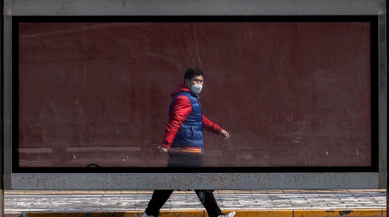 Ein Mann trägt einen Mundschutz und geht eine leere Werbefläche entlang.