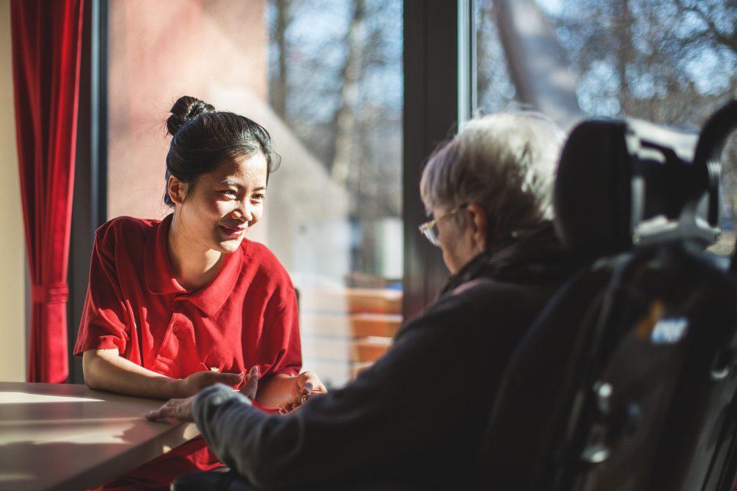 Eine junge Frau aus Vietnam arbeitet als Pflegekraft in Deutschland.