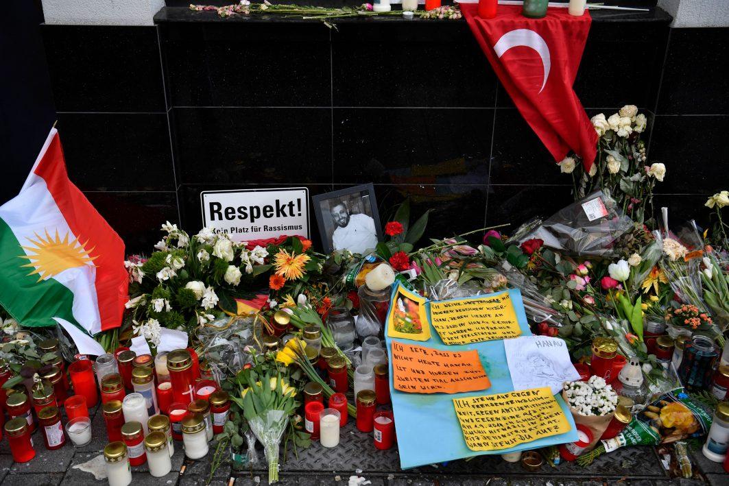 Viele Kerzen, Blumen, Bilder und Flaggen zum Gedenken der Opfer in Hanau stehen gesammelt auf dem Boden