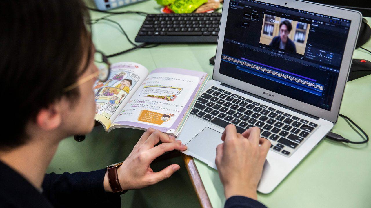 Lehrer sitzt mit aufgeklappten Schulbuch und Laptop am Schreibtisch