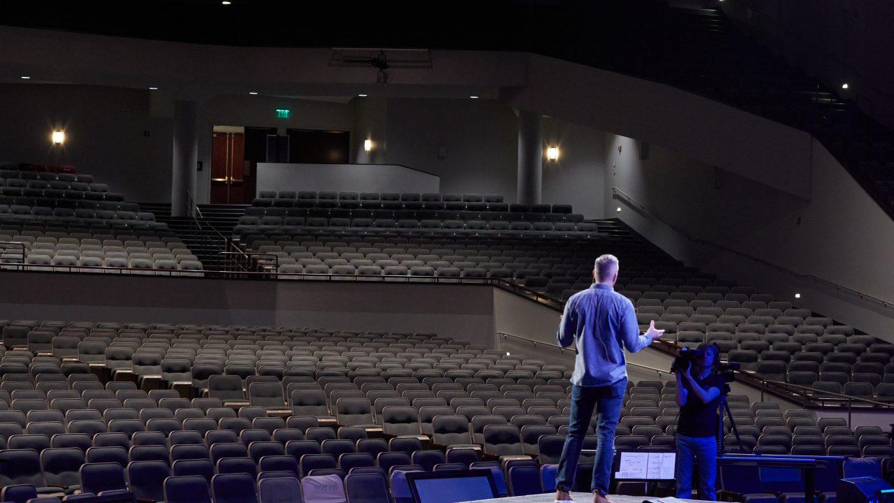 Mann steht auf der Bühne eines leeren Saals und spricht in eine Kamera
