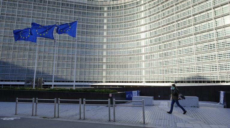 Frau mit Mundschutz läuft alleine am Gebäude der EU-Kommission vorbei