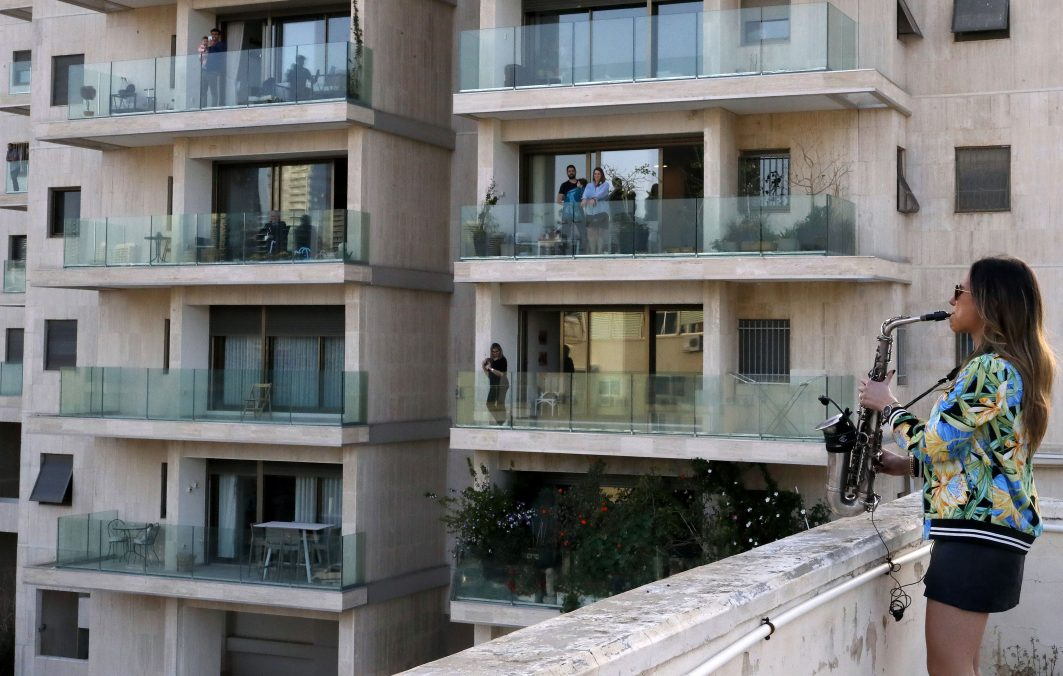 Frau spielt Saxophon auf ihrem Balkon. Die Nachbarn schauen jeweils von ihrem Balkon zu