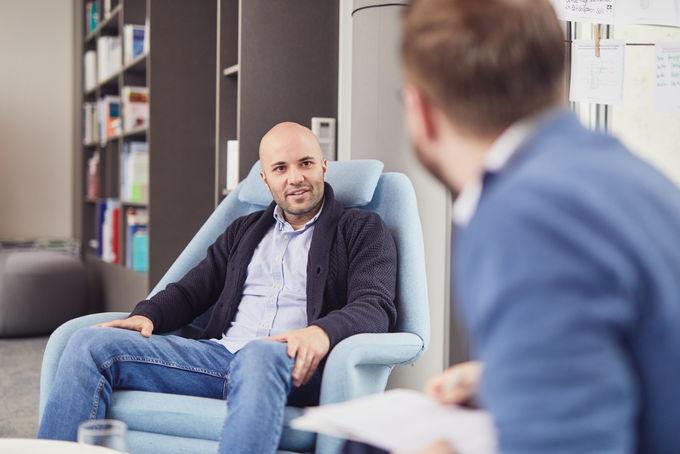 Der Research Fellow für Technologie und Außenpolitik bei der DGAP Kaan Sahin sitzt während eines Interviews auf einem Stuhl neben einem Bücherregal.