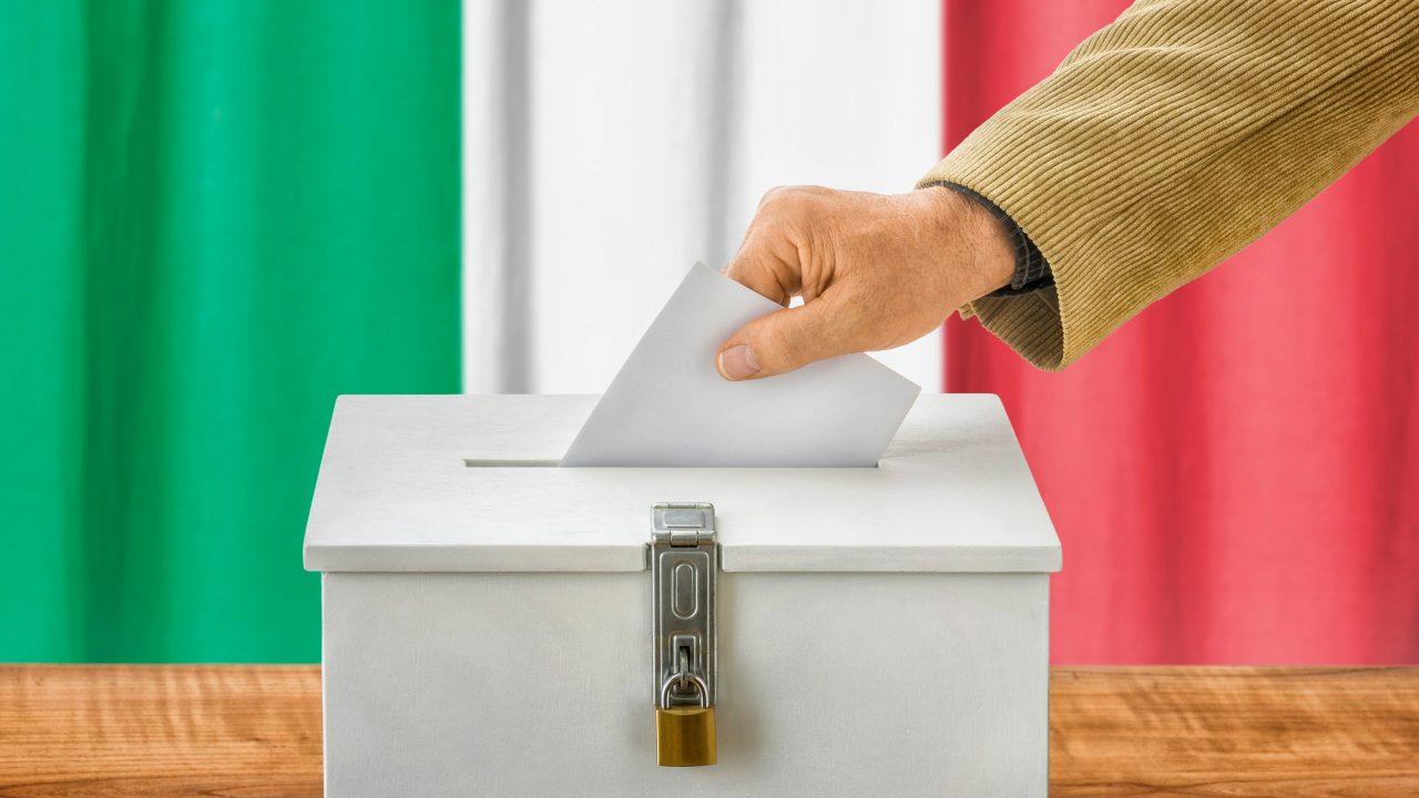 Ein Wahlzettel fällt in die Wahlurne, im Hintergrund die italienische Flagge