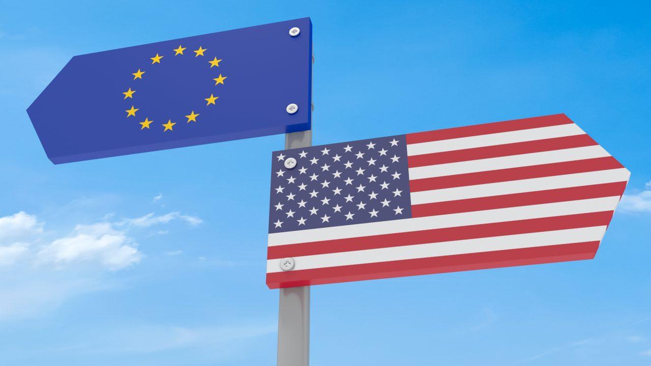 Zwei Wegweiser, EU und USA, weisen in entgegengesetzte Richtungen.
