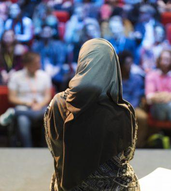 Sprecherin mit Kopftuch vor Publikum