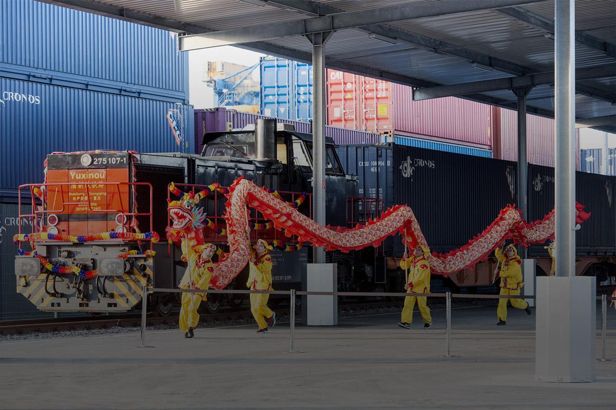 Mehrere Personen tragen in China einen gebastelten, langen Drachen auf ihren Schultern an einem Laster und Containern eines Unternehmens vorbei.