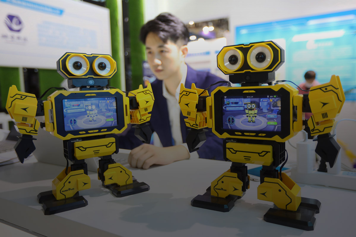 Zwei kleine, gelbe Roboter auf einer Messe in China.