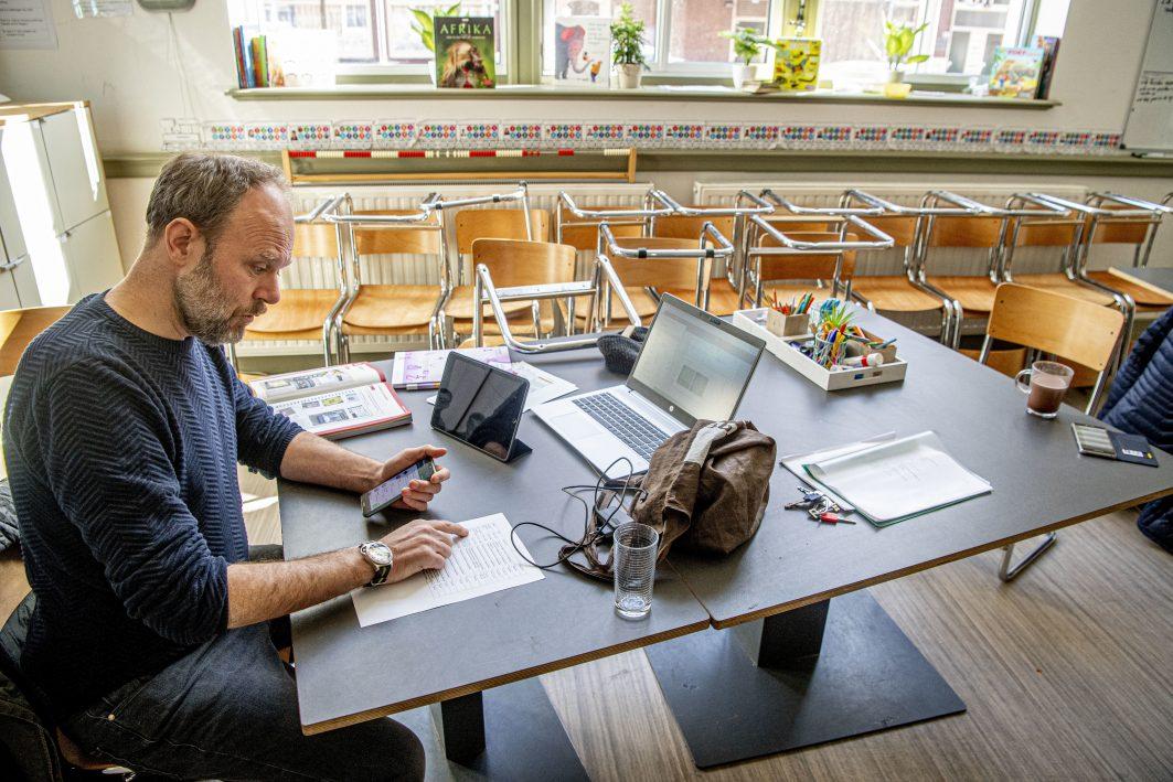 Lehrer sitzt mit Laptop in einem leeren Klassenzimmer