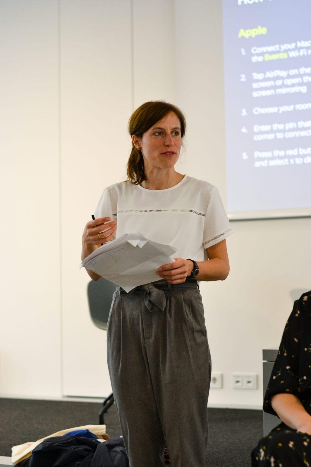 Die Programmleiterin von Work4Germany Maria Blöcher steht mit einem Zettel in der Hand vor einer an die Wand projizierten Präsentation.