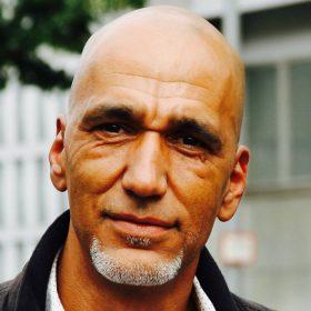 Porträt von Tahir Della. Er ist Sprecher der Initiative Schwarze Menschen in Deutschland, die sich bei den neuen deutschen organisationen (ndo) engagiert.