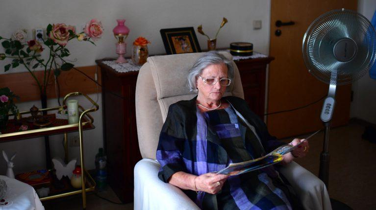 Hitzesommer, Seniorin im Sessel mit Ventilator
