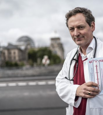 Dr. Eckhart von Hirschhausen steht in einem weißen Kittel, mit einem Stethoskop um den Hals und einem Zettel mit einem Fieberthermometer in der Hand vor dem Deutsche Bundestagsgebäude in Berlin.