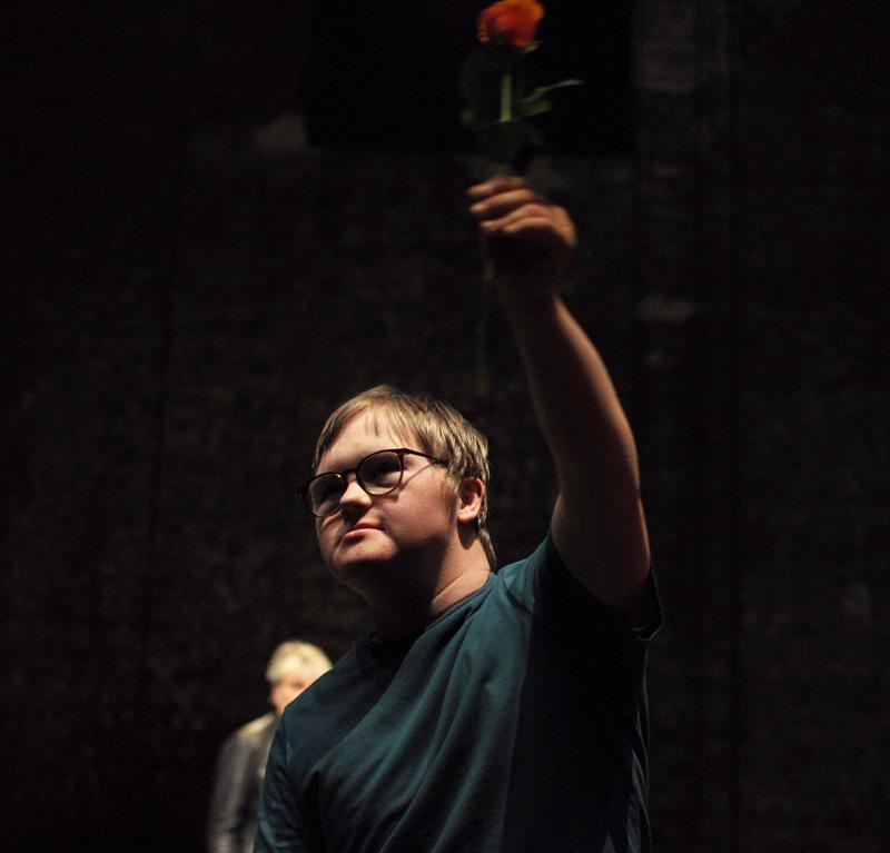 Ein Schüler hält auf der Bühne des Franz Sales Haus in Essen eine Rose in die Luft.