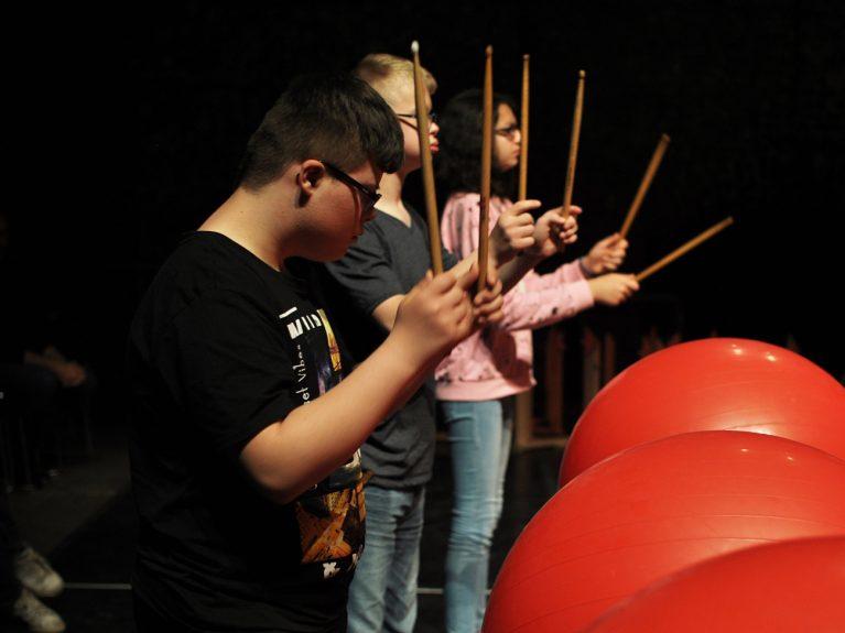 12- bis 16-jährigen Schüler*innen trommeln im Rahmen des Projekts Varieté Inklusiv am Franz Sales Haus in Essen mit Schlagzeugstöcken auf rote Gymnastikbälle.