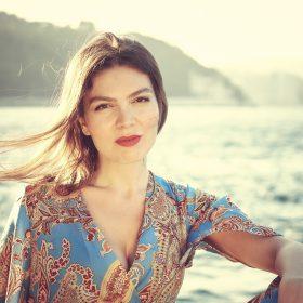 Die Juristin, Schauspielerin und Autorin Dilşad Budak-Sarıoğlu sitzt auf einem Strand. Im Hintergrund sind das Meer und ein paar Hügel zu sehen.