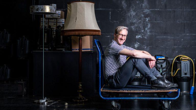 Theaterpädagoge Markus Höller sitzt auf einem Rollwagen hinter der Bühne. Neben ihm stehen Requisiten.