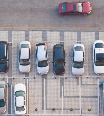 Mehrere Autos auf einem Parkplatz aus der Vogelperspektive.