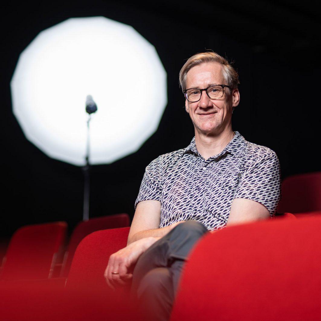 Der Theaterpädagoge Markus Höller sitzt in einem Theatersaal auf einem Sitz im Publikumsraum.