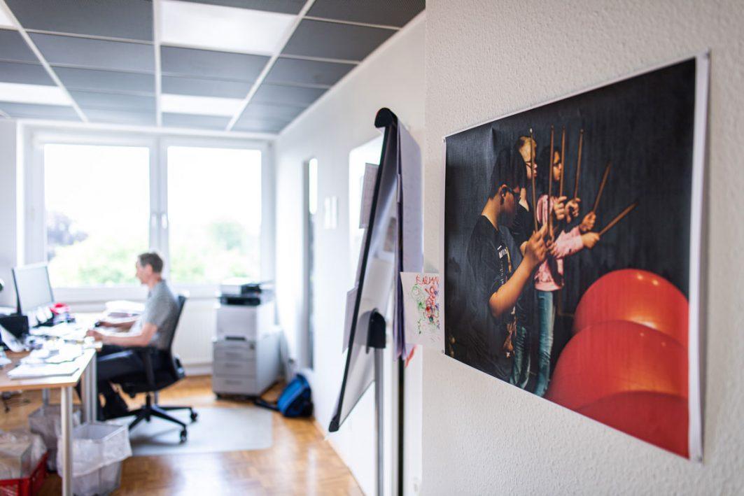 Ein Büro mit einem Bild an der Wand, auf dem Kinder ein Theaterstück vorführen.