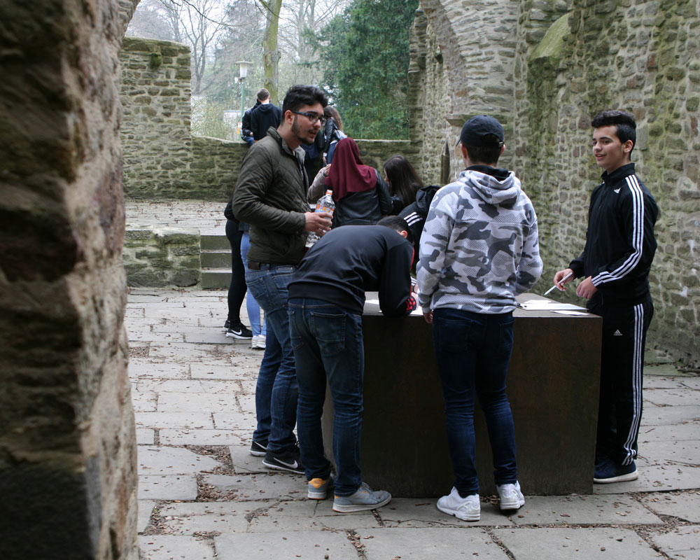 Vier Jugendliche stehen um einen Tisch in einer Burgruine, schreiben Dinge auf Zetteln vor ihnen und diskutieren.
