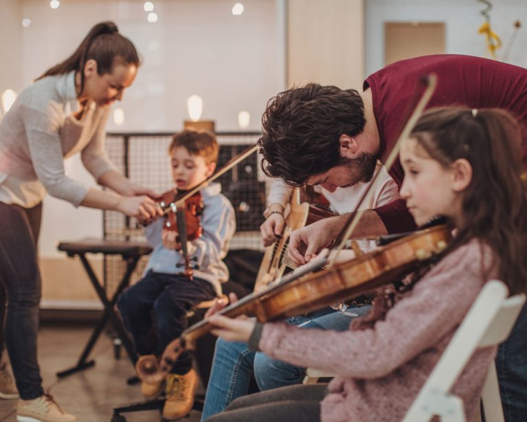 Eine Erwachsene Frau hilft einem kleinen Jungen beim Halten eines Geigenbogens und ein Mann hilft einem älteren Kind beim Halten der Gitarrensaiten. Im Vordergrund sitzt ein Mädchen und spielt Geige.