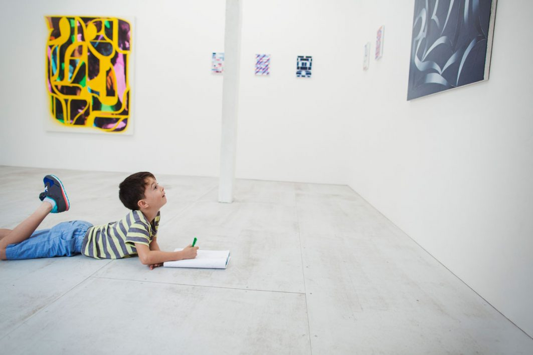 Ein Junge liegt mit dem Bauch auf dem Boden in einer Kunstgalerie vor einem abstrakten Gemälde. Während er das Gemälde betrachtet, schreibt er in ein Heft rein.