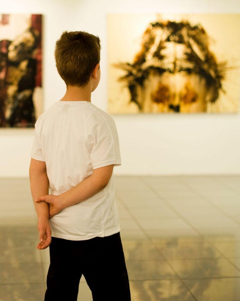 Ein Junge steht vor einem abstrakten Gemälde in einer Kunstgalerie.