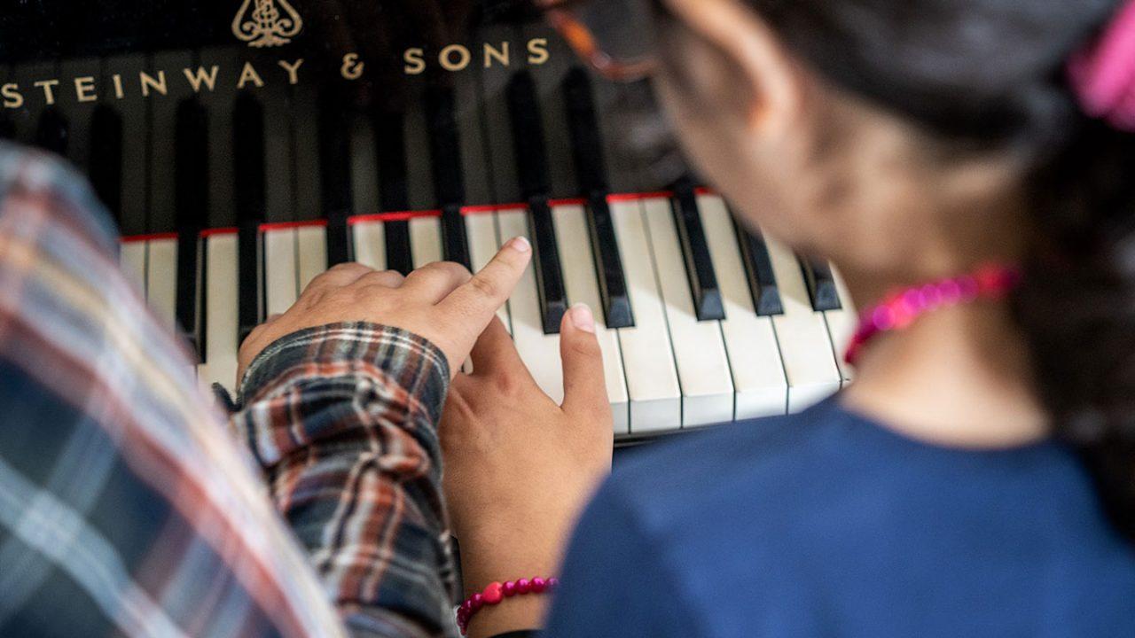 Die Schwestern Manar und Ikram von der Gemeinschaftsgrundschule Sandstraße in Duisburg-Marxloh üben auf einem Klavier zu spielen.
