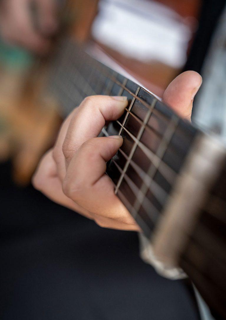 Sofia von der Gemeinschaftsgrundschule Sandstraße in Duisburg-Marxloh spielt auf einer Gitarre.