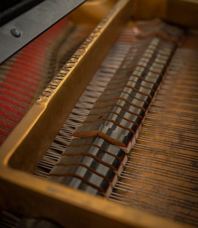 Die Tasten eines Klaviers unter dem Klavierdeckel.