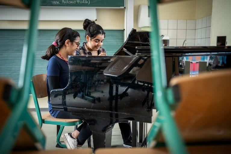 Die Schwestern Manar und Ikram spielen auf einem großen Flügel.