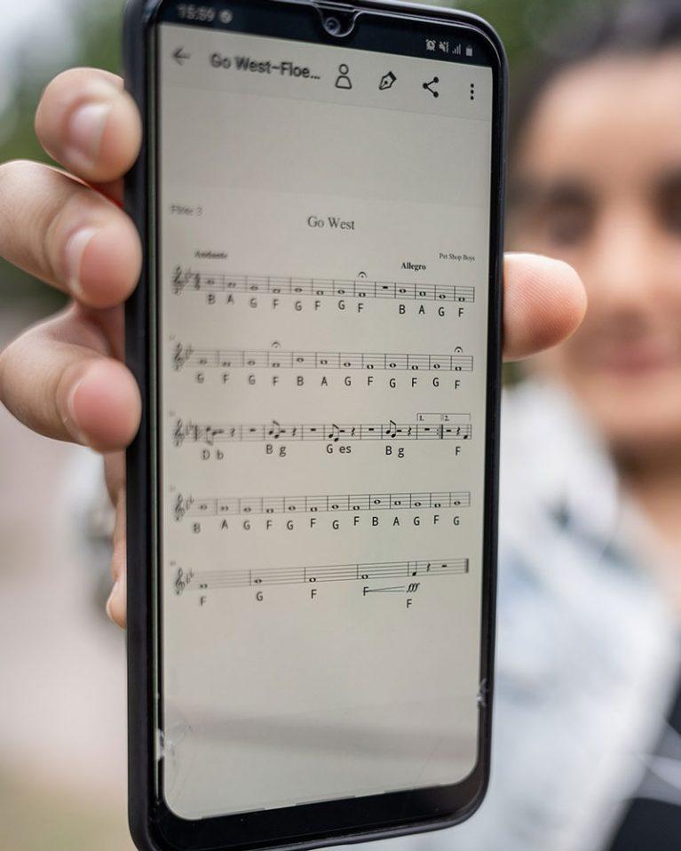 """Die 14-jährige Ikram hält ein Smartphone in die Kamera, auf dem ein Notenblatt zu dem Song """"Go West"""" zu sehen ist."""